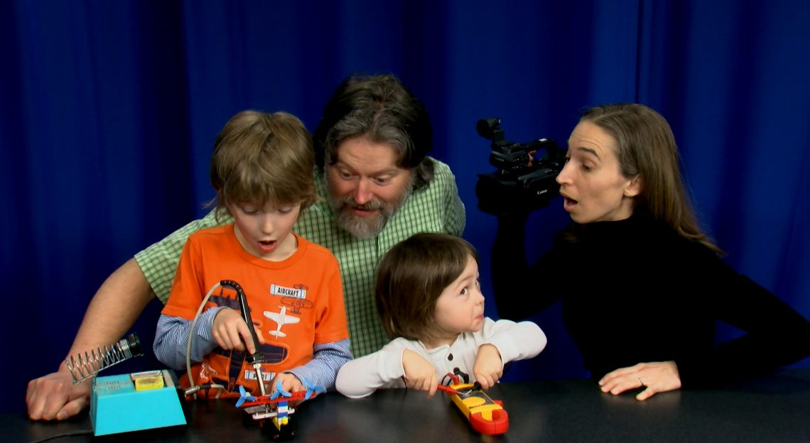 Man, woman, and two boys using electronic equipment