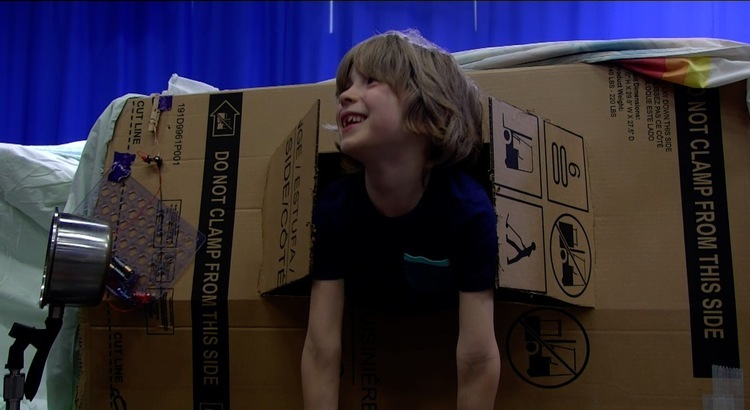 Boy smiling from the window of a cardboard box fort with a doorbell made from an electromagnet circuit and pot