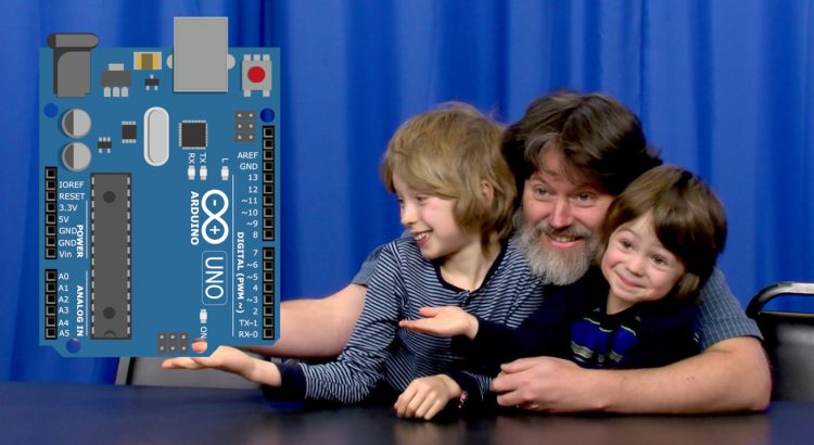 Man and two boys holding a super-sized Arduino Uno