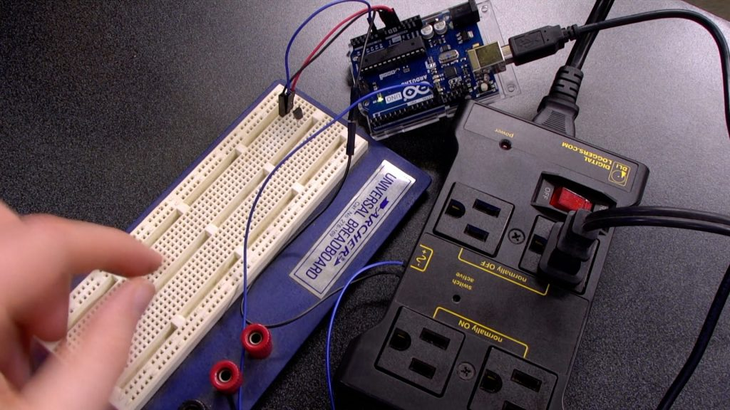 Breadboard with temperature sensor and jumper wires to Arduino Uno, which is also wired to the IOT relay.