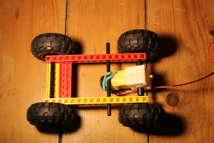 Image of bottom of robot body showing four wheels attached to axles through rails, two flat plate pieces on the front of the rails and the motor attached to axles at the back.