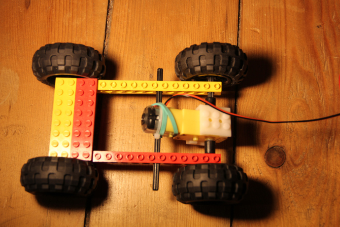 Image of top of robot body showing four wheels attached to axles through rails, two flat plate pieces on the front of the rails and the motor attached to axles at the back.