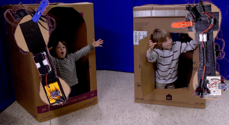 Two boys in box forts with huge DIY cardboard telephones