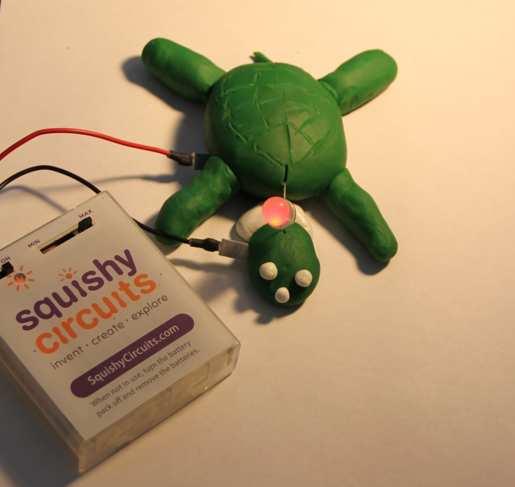 Green play dough turtle with pink LED and Squishy Circuits battery pack.