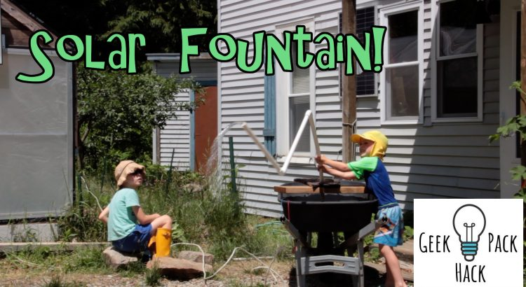 Boys with DIY solar fountain in a wheel barrow