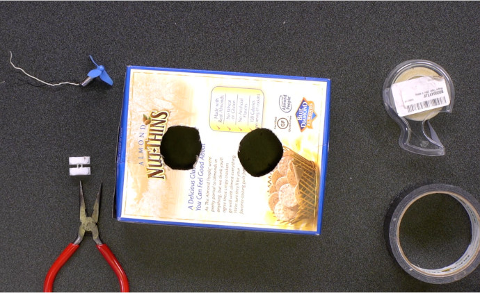 Cracker box with two holes, each approximately the size of a drone propeller.